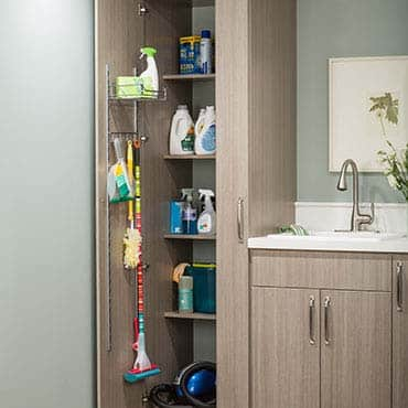 Laundry closet with open cabinet with cleaning products inside