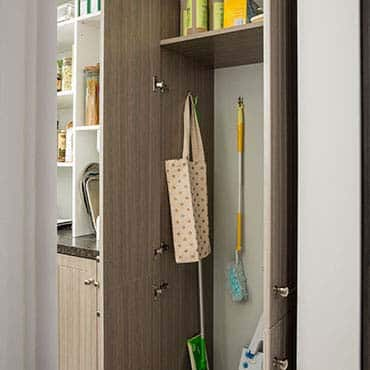 Open cabinet in pantry displaying cleaning items