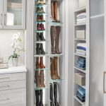 Corner view of closet showing clothing on shelves and shoes on glass shelves