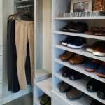 Closet with shoes on shelves and clothing on racks and mirror