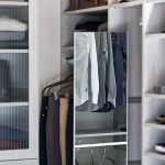 Close up of closet with shelves and clothing on racks