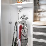 Garage closet with open door showing golf equipment inside