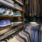 Close up of Inspired Closets closet with shoes on shelves and shirts on clothing racks