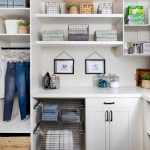 Custom floor mounted boutique laundry room storage with pull out hampers