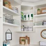 Custom floor mounted boutique laundry room storage with corner shelving